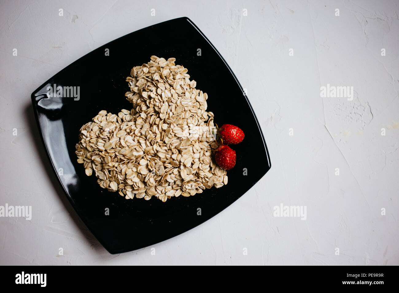 top view oat flakes in the form of a heart on a black plate and fresh strawberries Stock Photo