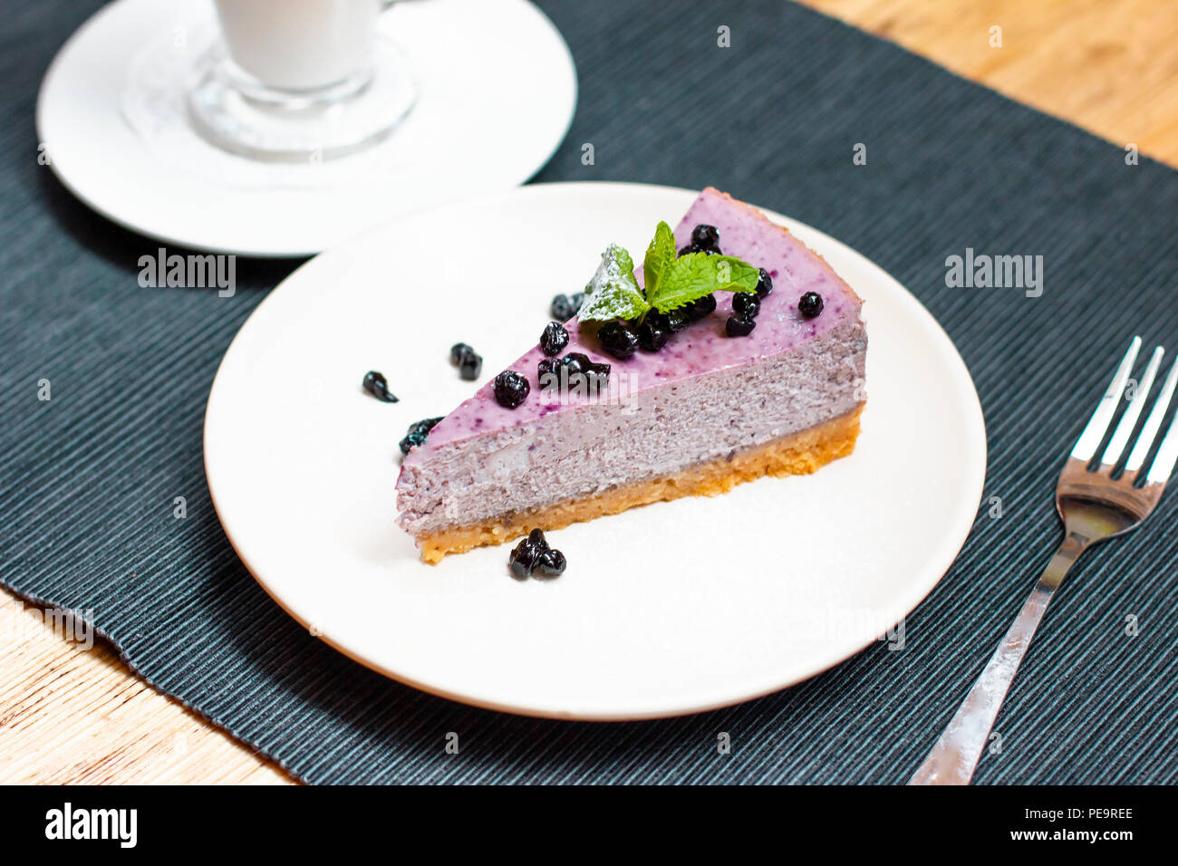 Blueberry cheesecake with berries and mint with coffee latte on the table - Stock Image