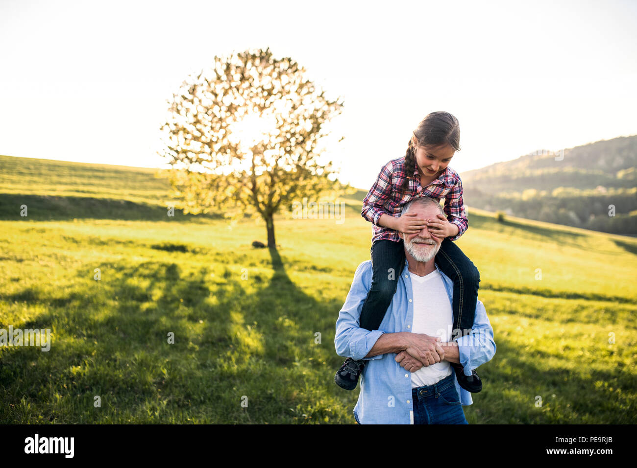 A senior grandfather giving a small granddaughter a piggyback ride in nature. - Stock Image