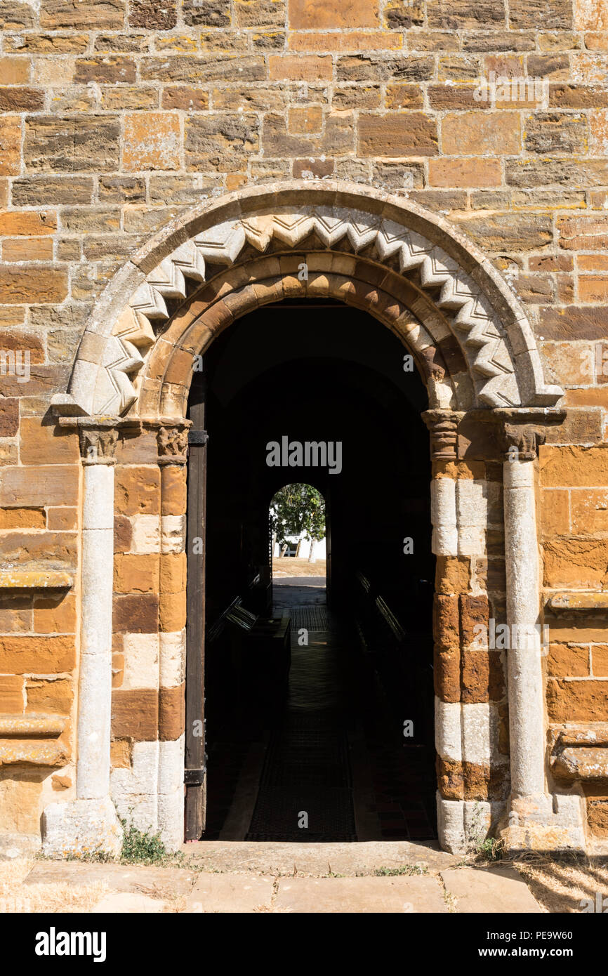 Spratton, Northamptonshire, 24-07-18. An open door in a wall is surmounted by a carved Norman arch. Inside is darkness and a doorway letting in light. - Stock Image
