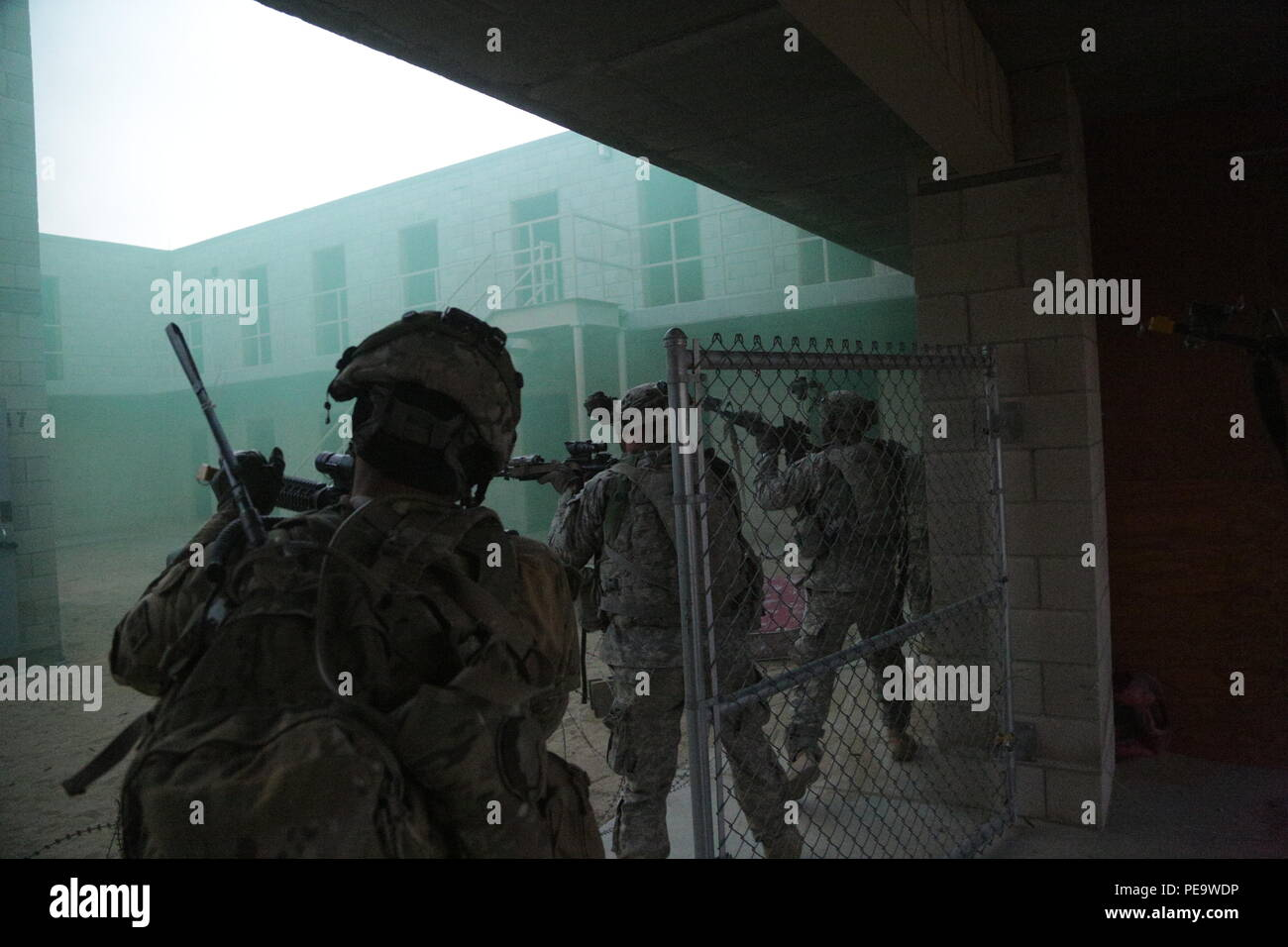 U.S. Soldiers assigned to 2nd Battalion, 12th Infantry Brigade Combat Team, 4th Infantry Division, infiltrate a prison compound overrun by the enemies during Decisive Action Rotation 16-02 at the National Training Center, Fort Irwin, Calif., Nov. 13, 2015. Decisive Action Rotations are designed to give soldiers real-life experience before deployment. (U.S. Army photo by Pfc. Christopher Lett) - Stock Image