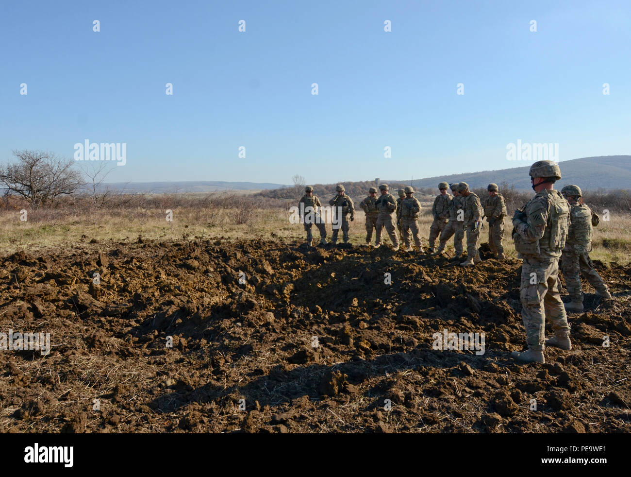 Soldiers of 1st Armored Brigade Combat Team, attached to 5th Squadron, 7th Cavalry Regiment, 3rd Infantry Division, stationed at Fort Stewart, Ga., rally around the crater they just made with 100 pounds of explosives during a field training exercise in support of Operation Atlantic Resolve at Novo Selo Training Center, Bulgaria, Nov. 19, 2015. Cratering charges are used in order to quickly create an obstacle in a tactical scenario and to deny the enemy freedom of maneuver. (U.S. Army photo by Staff Sgt. Steven M. Colvin/Released) - Stock Image