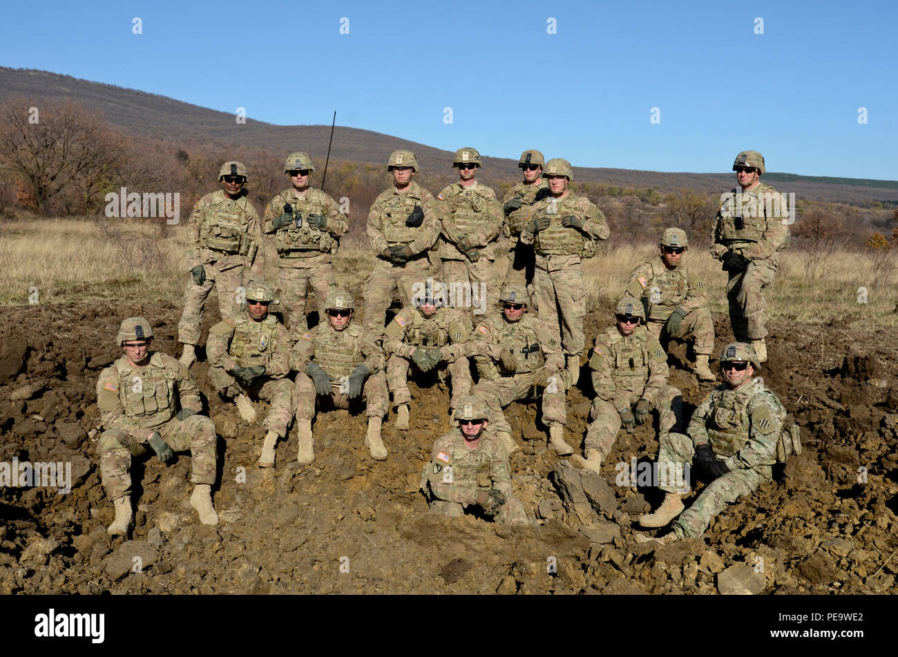 Soldiers of 1st Armored Brigade Combat Team, attached to 5th Squadron, 7th Cavalry Regiment, 3rd Infantry Division, stationed at Fort Stewart, Ga., pose for a group photo around the crater they just made with 100 pounds of explosives during a field training exercise in support of Operation Atlantic Resolve at Novo Selo Training Center, Bulgaria, Nov. 19, 2015. Cratering charges are used in order to quickly create an obstacle in a tactical scenario and to deny the enemy freedom of maneuver. (U.S. Army photo by Staff Sgt. Steven M. Colvin/Released) - Stock Image