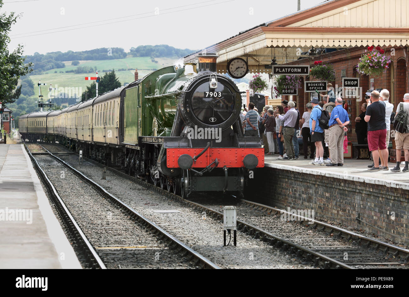 Steam enthusiasts fill platform 1 at Toddington station on the Gloucestershire Warwickshire Railway as a train to Broadway arrives. - Stock Image
