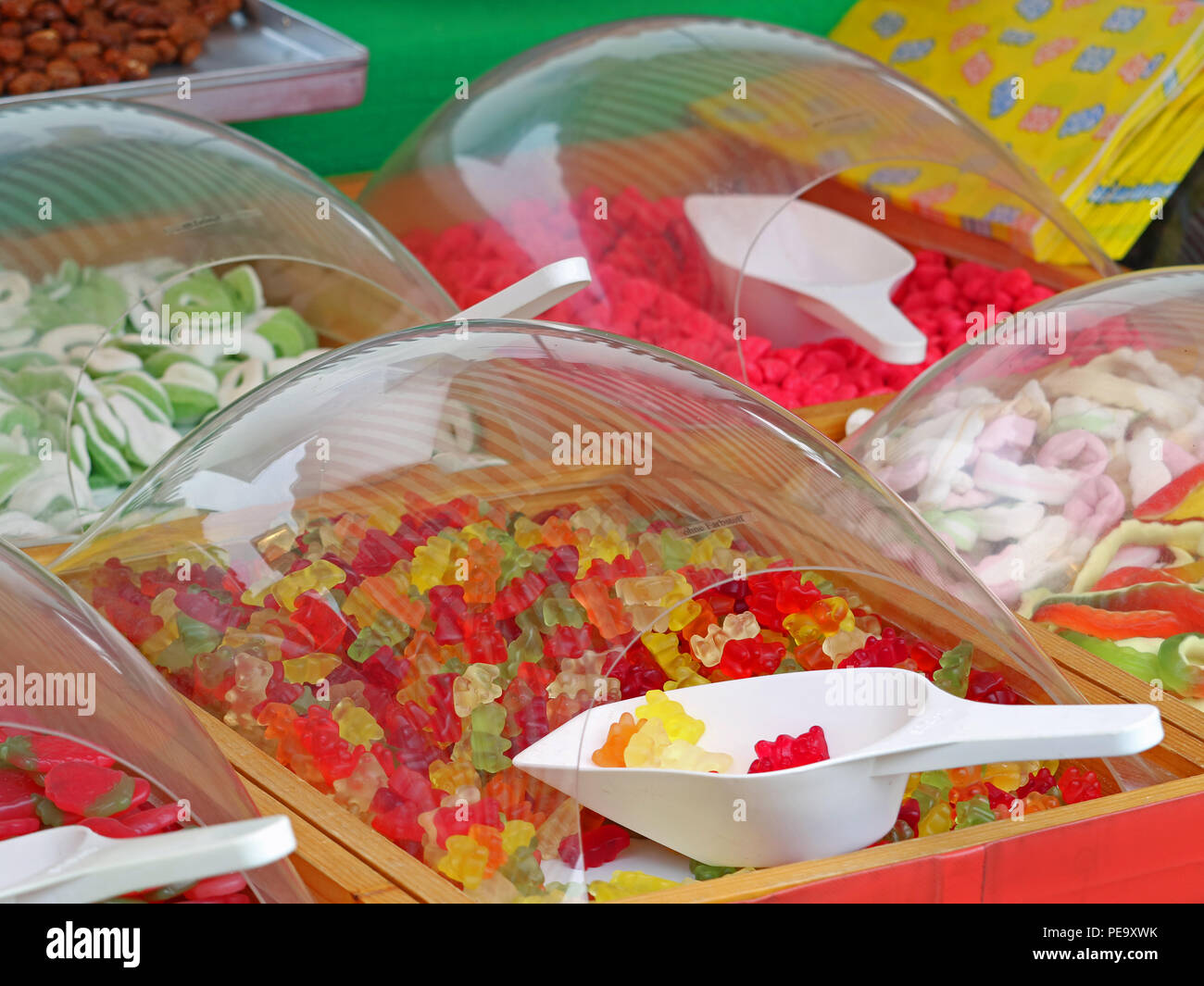 Close up of colorful gummy sweets bears in market with white plastic scoops Stock Photo