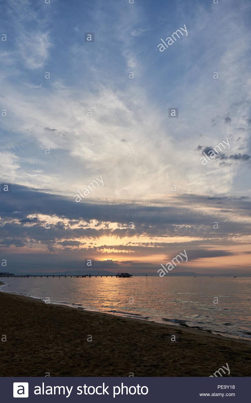 Amazing Sunset on the Sea. Adriatic sea with shore. Lignano Sabbiadoro, Italy. Beautiful sunset, waves and landscape. - Stock Image