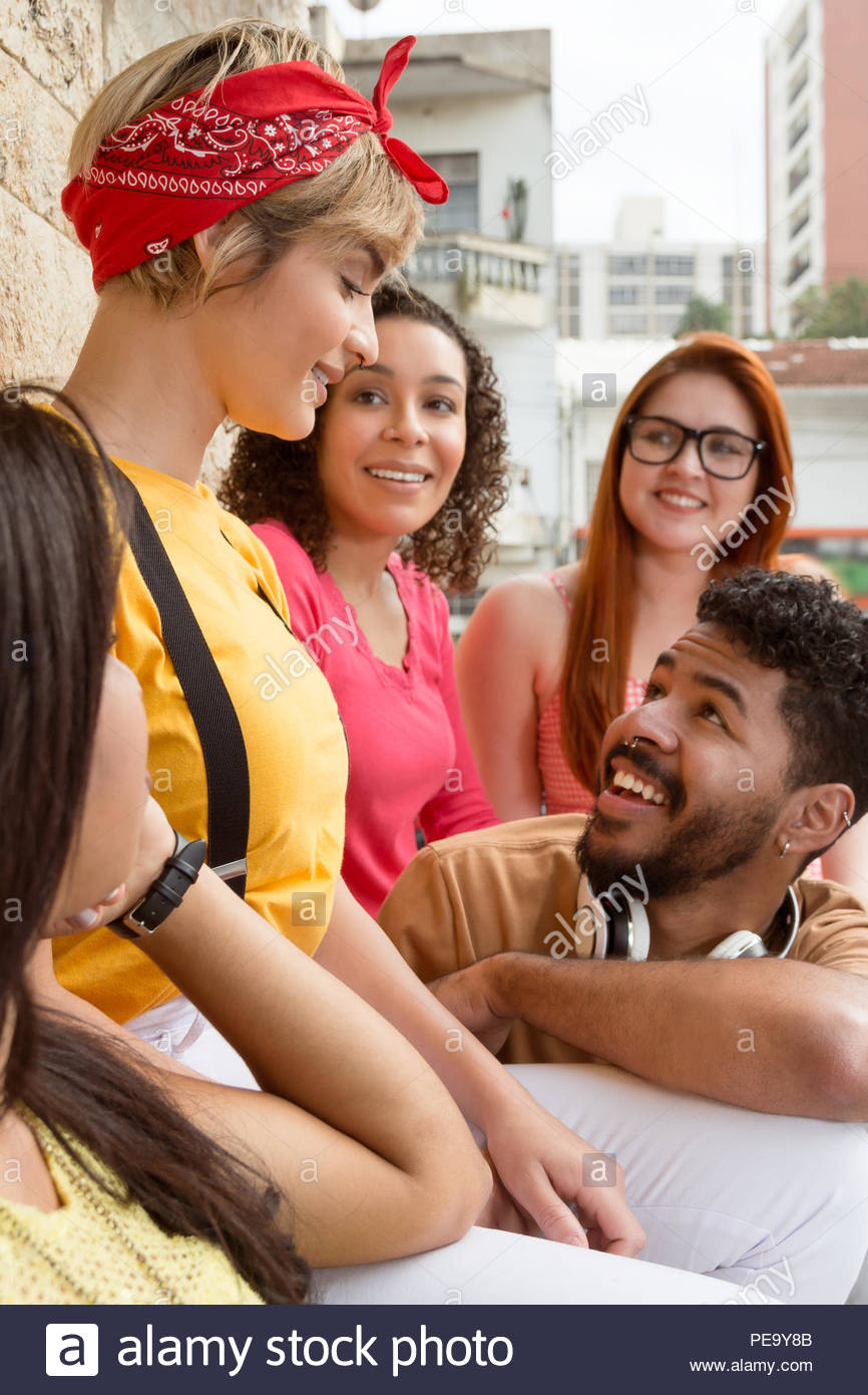 Mixed race people bonding at restaurant outside. Group of happy smiling students having a great time at cafe bar outdoor. Summer, warm, friendship, di - Stock Image