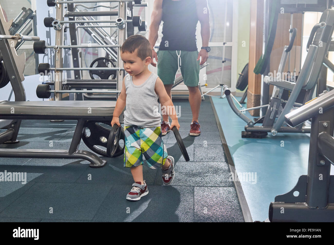 Little son helping his father on training in gym carrying