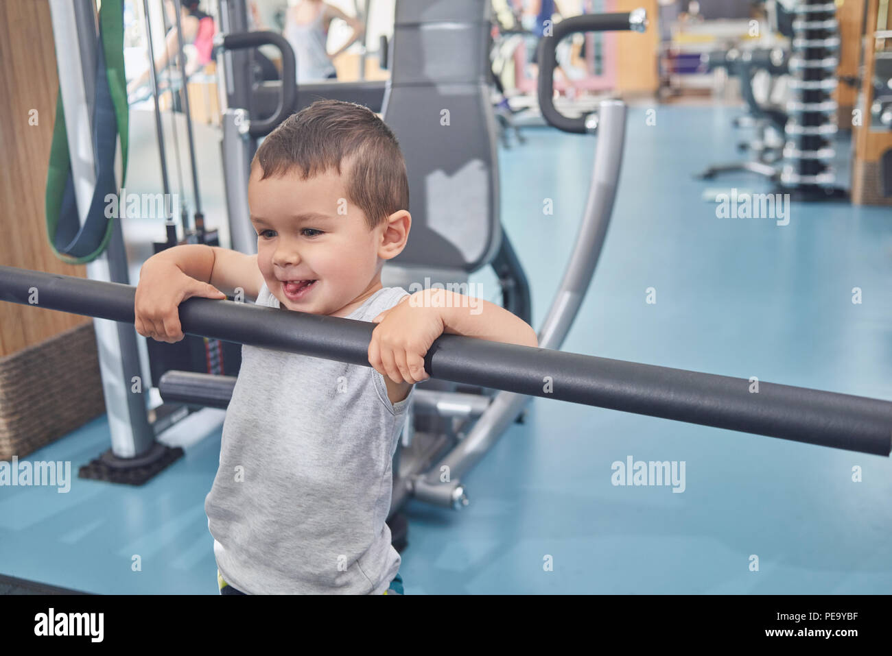Little cute boy grimacing, holding on metallic crossbar in gym. Child laughing, smiling, looking cute, happy, satisfied. Heavy simulators standing behind. Keeping healthy lifestyle. - Stock Image