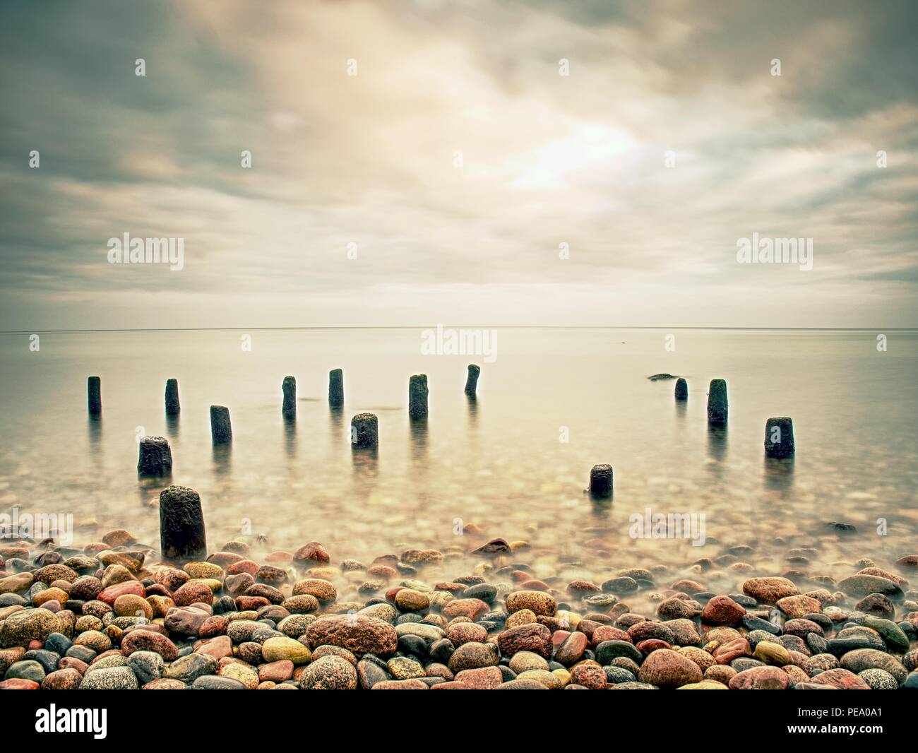 Romantic walk at silent ocean Mossy breakwater poles in smooth water of sea within windless. Stony beach - Stock Image