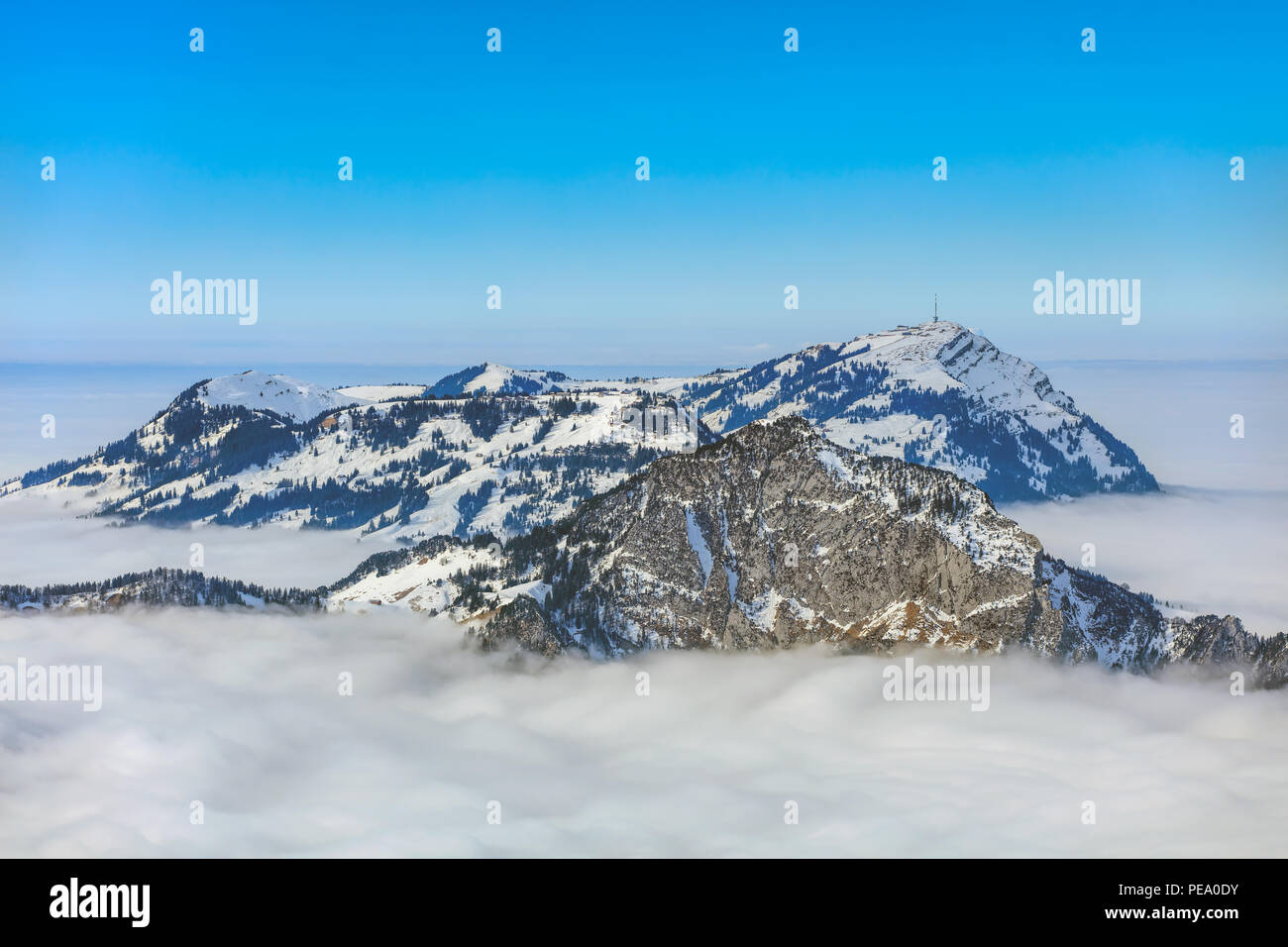 Summits of the Swiss Alps rising from sea of fog, the furthermost one is well-known Mt. Rigi - a wintertime view from Fronalpstock mountain in the Swi - Stock Image
