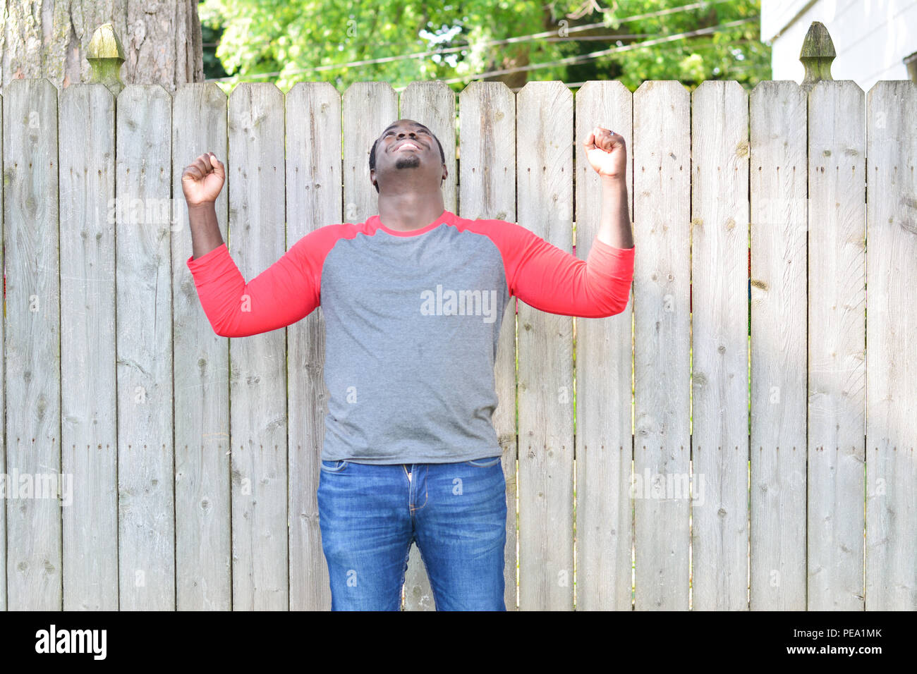 Celebrating black man in front of wooden fence - Stock Image