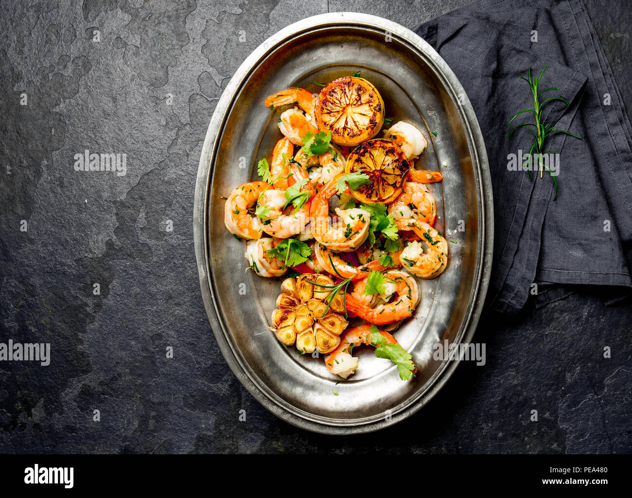 Grilled fried Shrimps Prawns on oval metal plate. Dark background. Top view - Stock Image