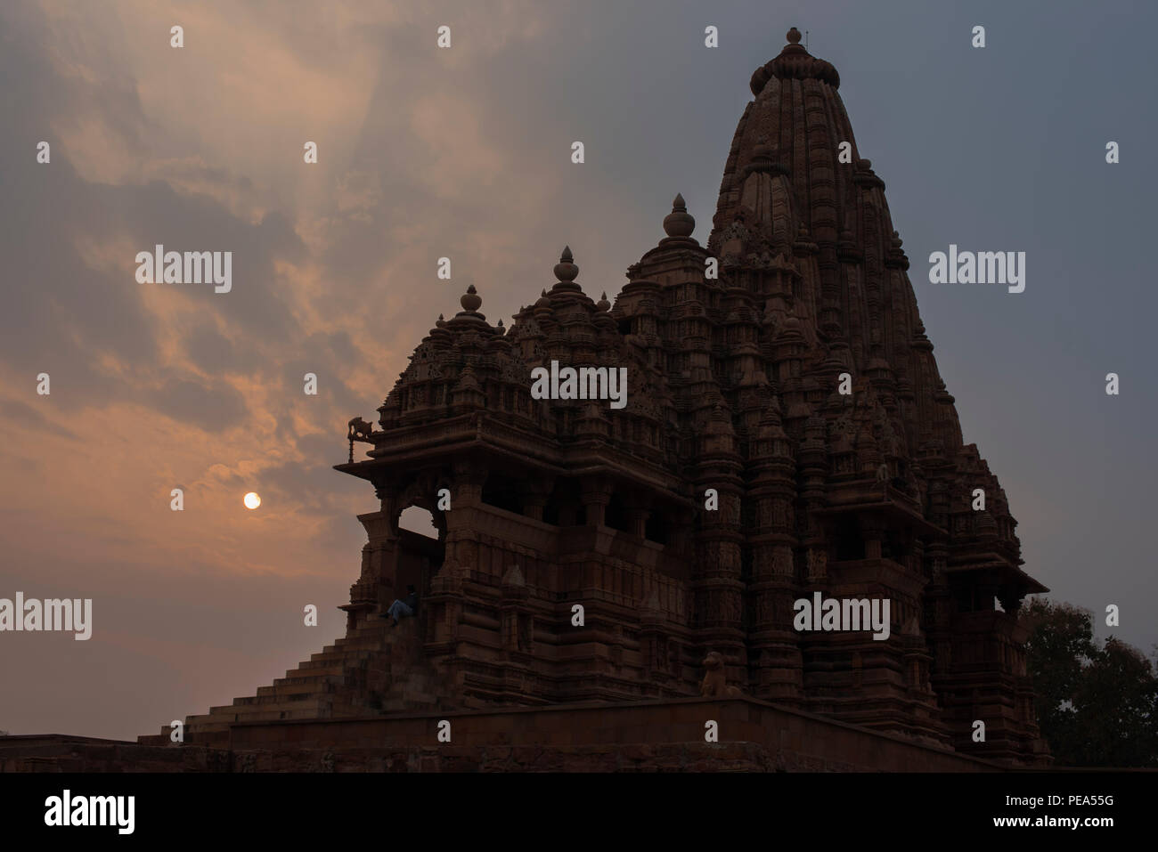 Ancient Kandariya Mahadev Temple with intricate carvings and statues against sunset dedicated to Hindu God Lord Shiva symbolizing power and strength - Stock Image