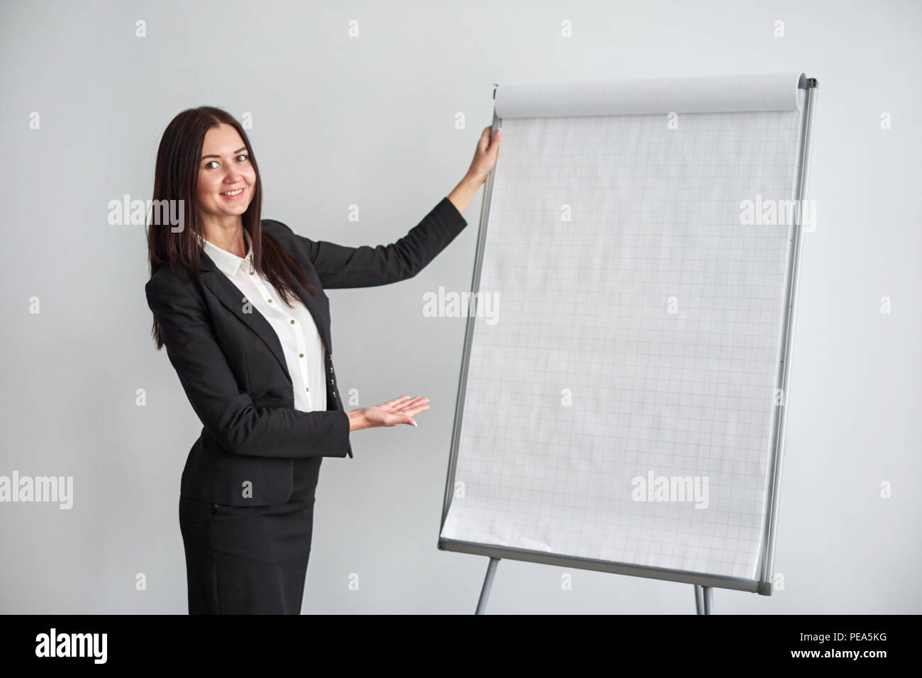 Portrait of young smiling businesswoman standing by flipchart in office - Stock Image