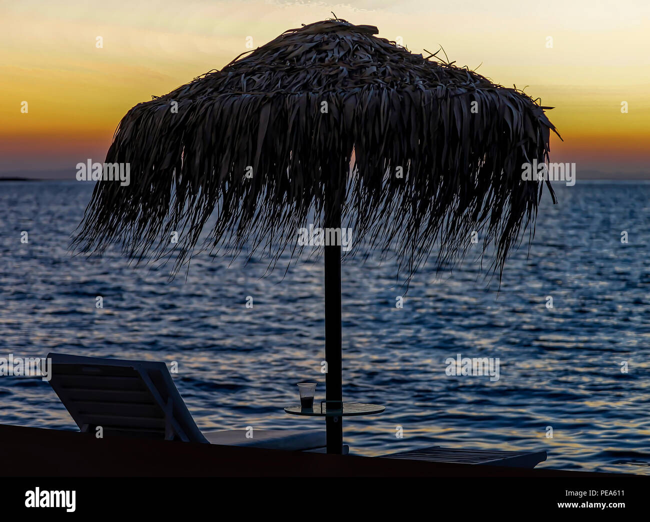 Beach Umbrella.  Silhouete of straw umbrellla and deckchair on beach on a Greek Island at sunset. Seascape Photography. Stock Image. - Stock Image