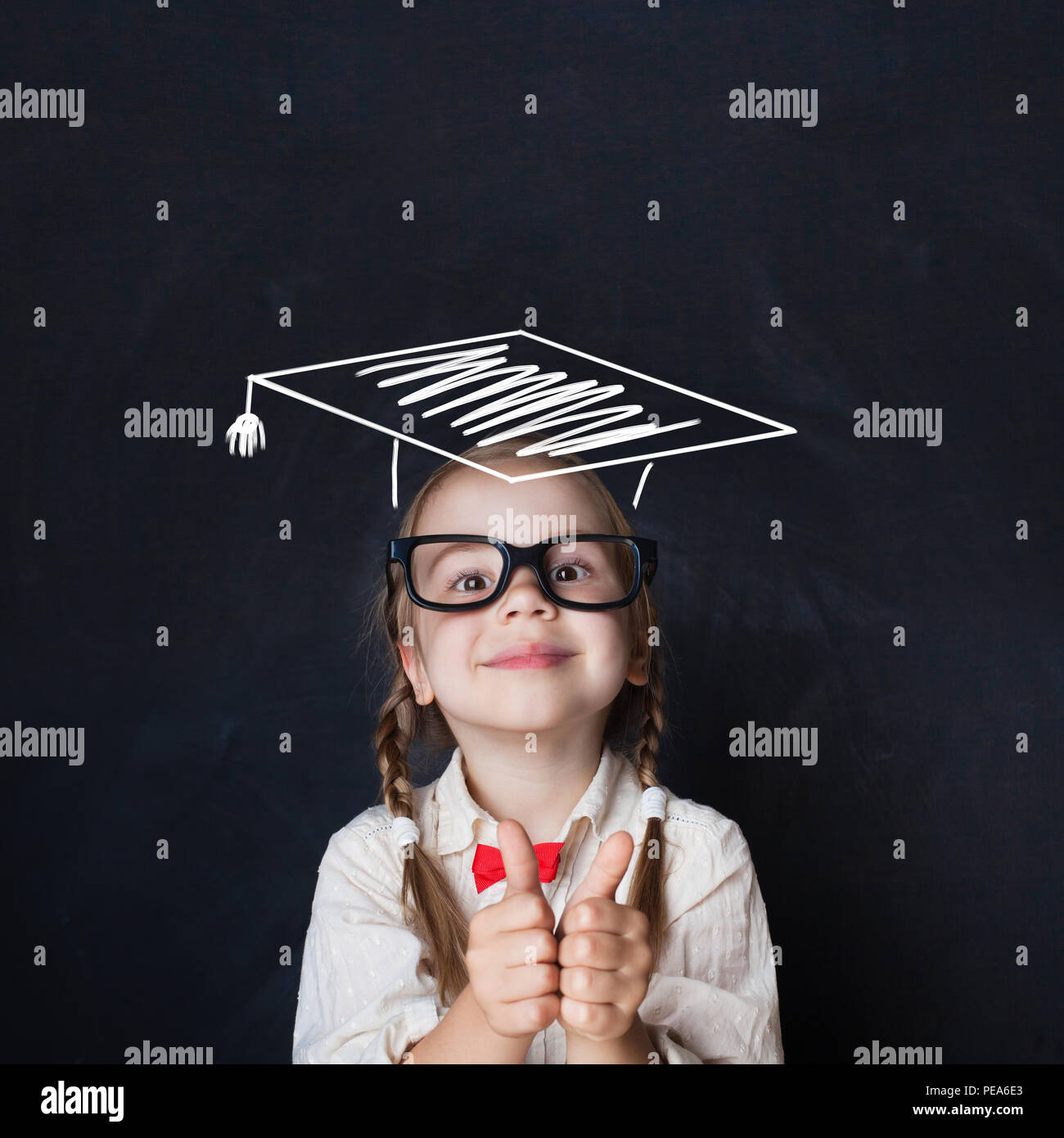 Little genius kid in  graduation hat with thumb up on chalkboard - Stock Image
