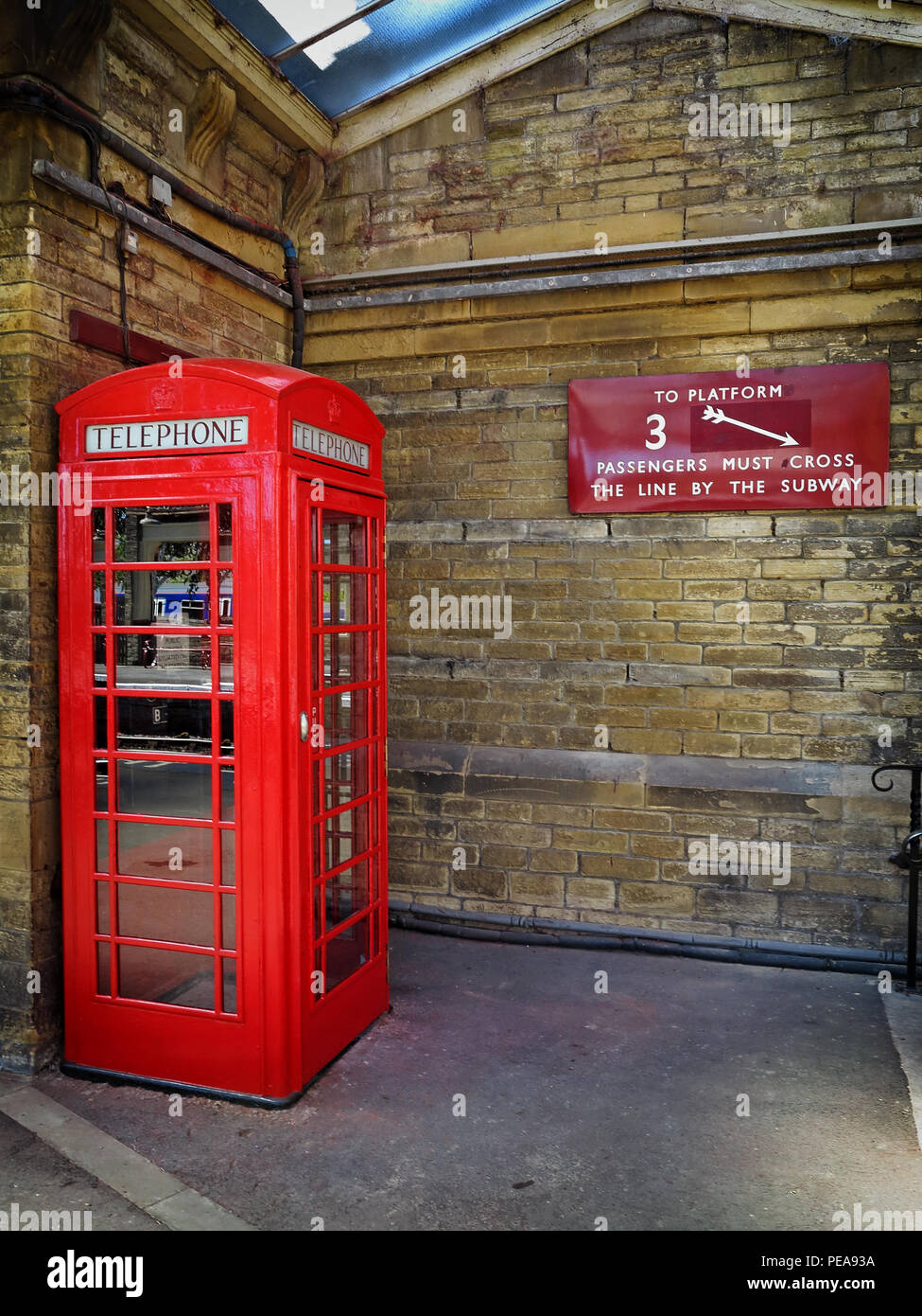 A historic red telephone box and platform sign at Keighley station - Stock Image