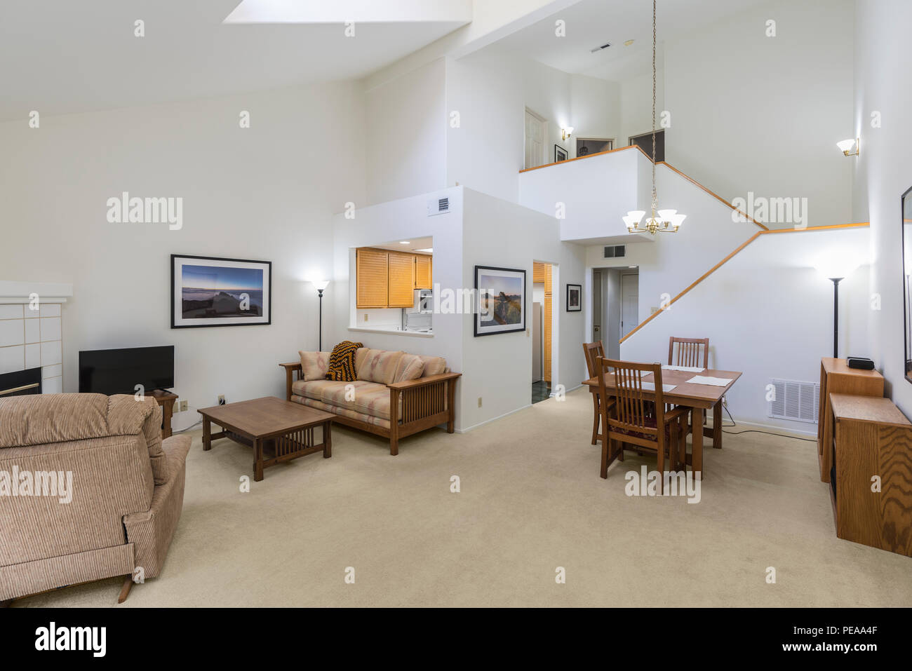 High ceiling condo living room.  Framed wall art is the photographers work and is included in the release. - Stock Image