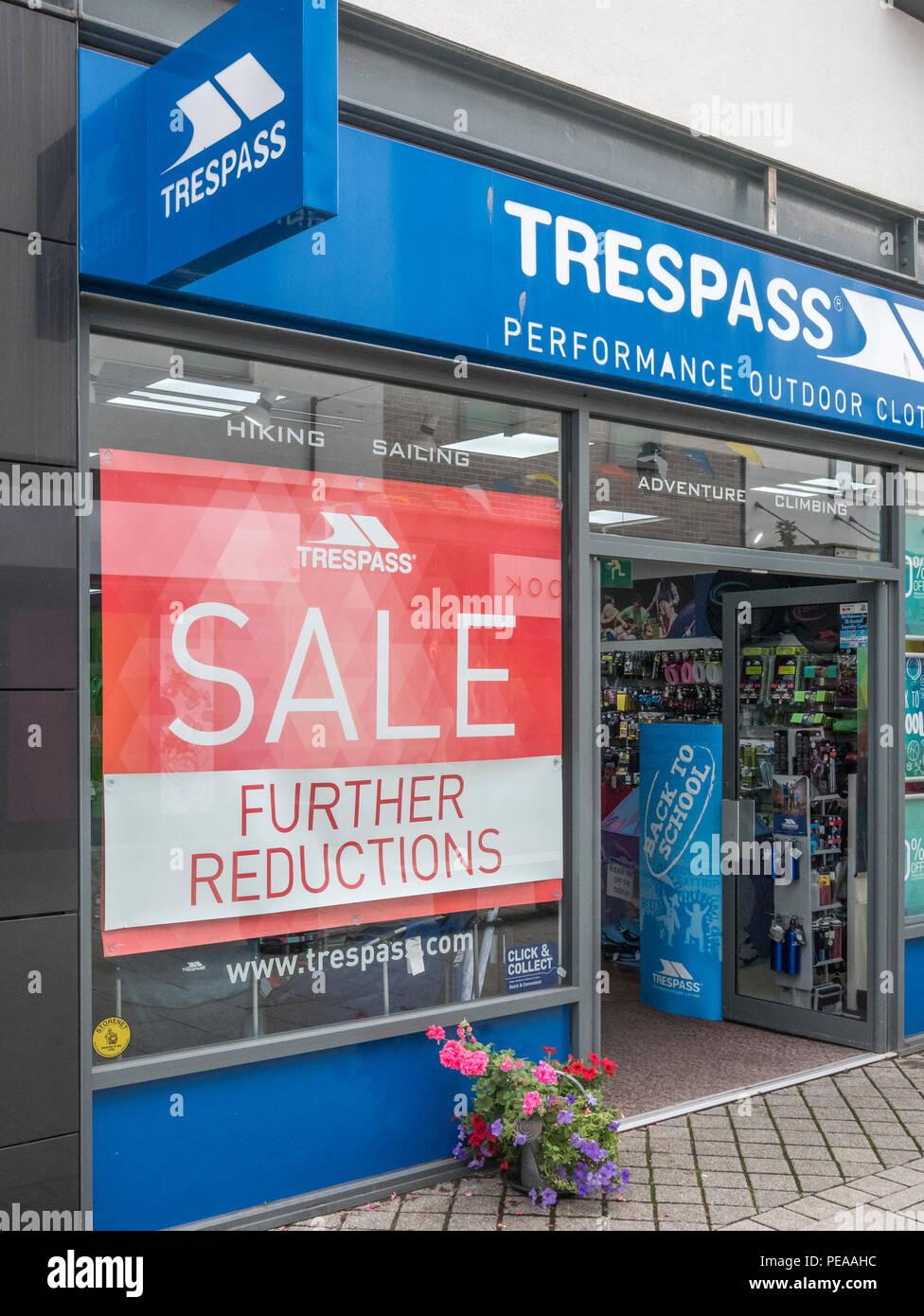 Summer sales sign in Trespass shop window (St. Austell, Cornwall). Metaphor high street squeeze. - Stock Image