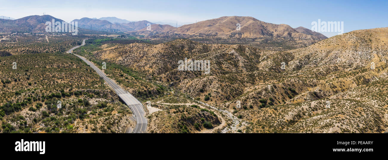 Highway leads into the rolling hills of the Californian Mojave Desert. - Stock Image