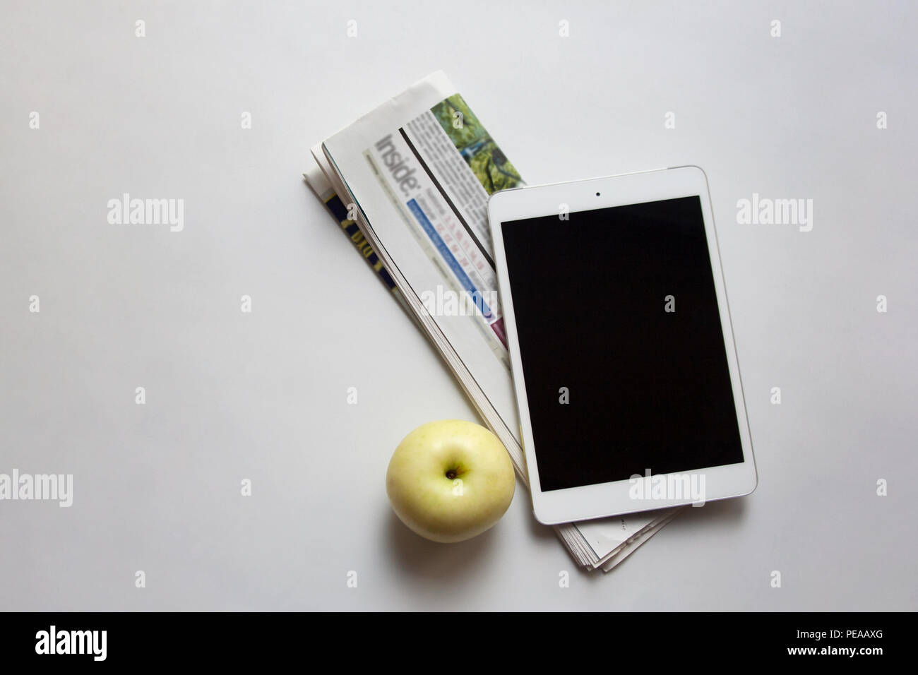 Digital tablet, folded newspaper and ripe apple isolated on white background with copy space Stock Photo