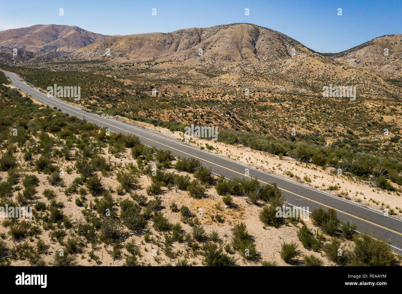 View of a desert roadway in the heart of the Mojave in southern California. - Stock Image
