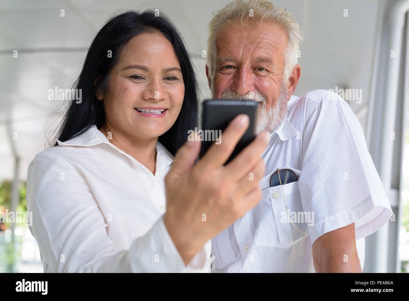 Mature multi-ethnic couple happy and in love while exploring the Stock Photo