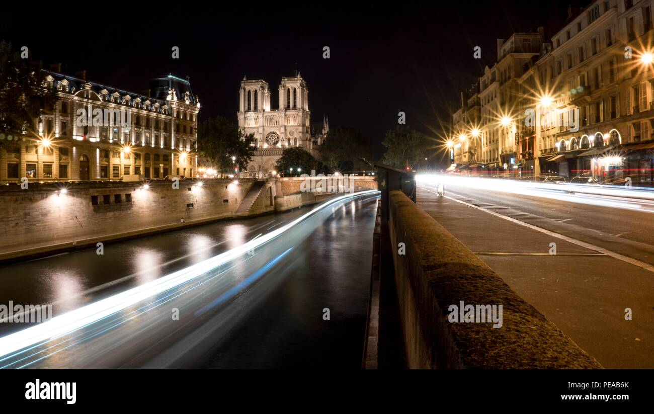 Notre Dame Cathedral of Paris at night with lights trails in the Seine River and the qua d'orleans - Stock Image
