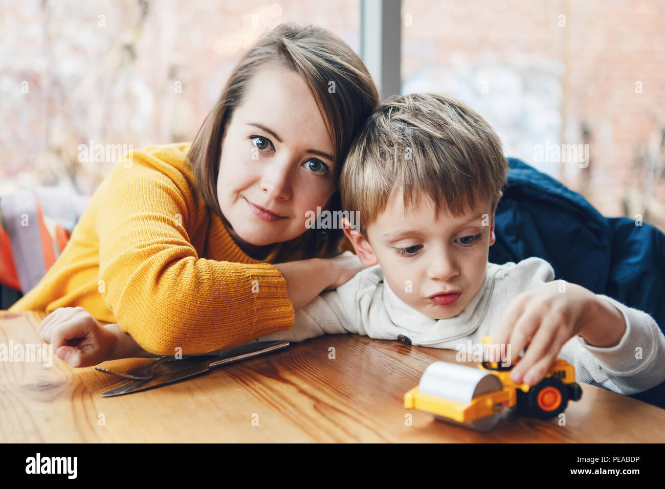 Portrait of white Caucasian happy family, mother and son, sitting in restaurant cafe at table, smiling playing with toy car, authentic lifestyle Stock Photo