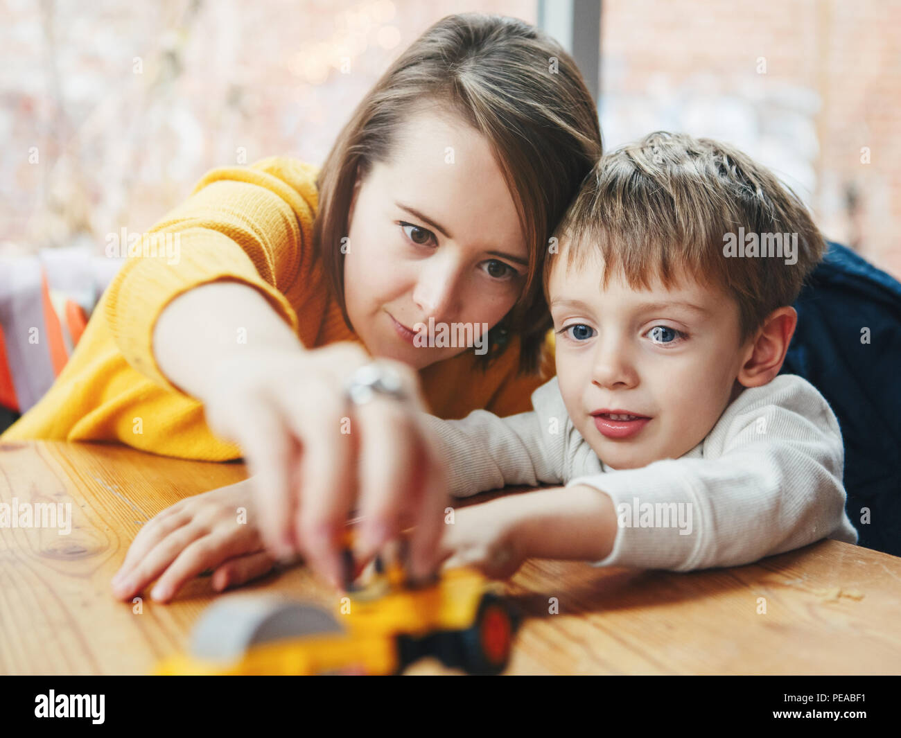 Portrait of white Caucasian happy family, mother and son, sitting in restaurant cafe at table, smiling playing with toy car, authentic lifestyle - Stock Image