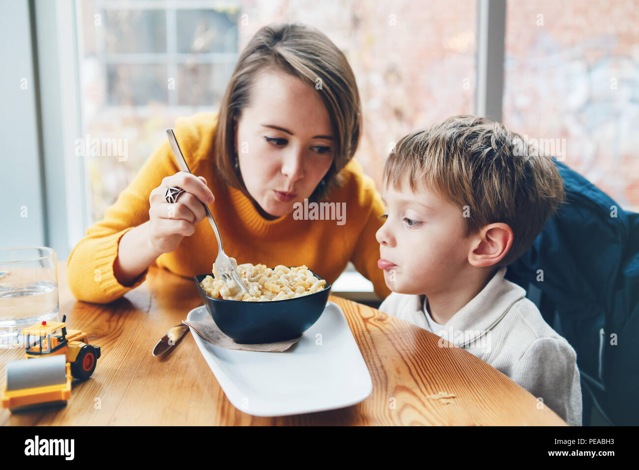 Portrait of white Caucasian happy family, mother and son, sitting in restaurant cafe at table, feeding eating pasta spaghetti, authentic lifestyle - Stock Image