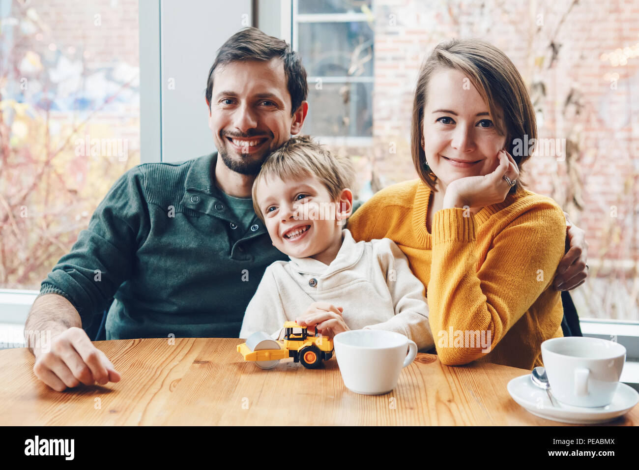 Portrait of white Caucasian happy family of three mother, father and son, sitting in restaurant cafe at table, smiling playing, authentic lifestyle - Stock Image