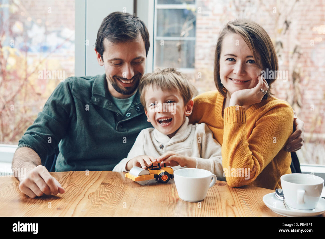 Portrait of white Caucasian happy family of three mother, father and son, sitting in restaurant cafe at table, smiling playing, authentic lifestyle Stock Photo