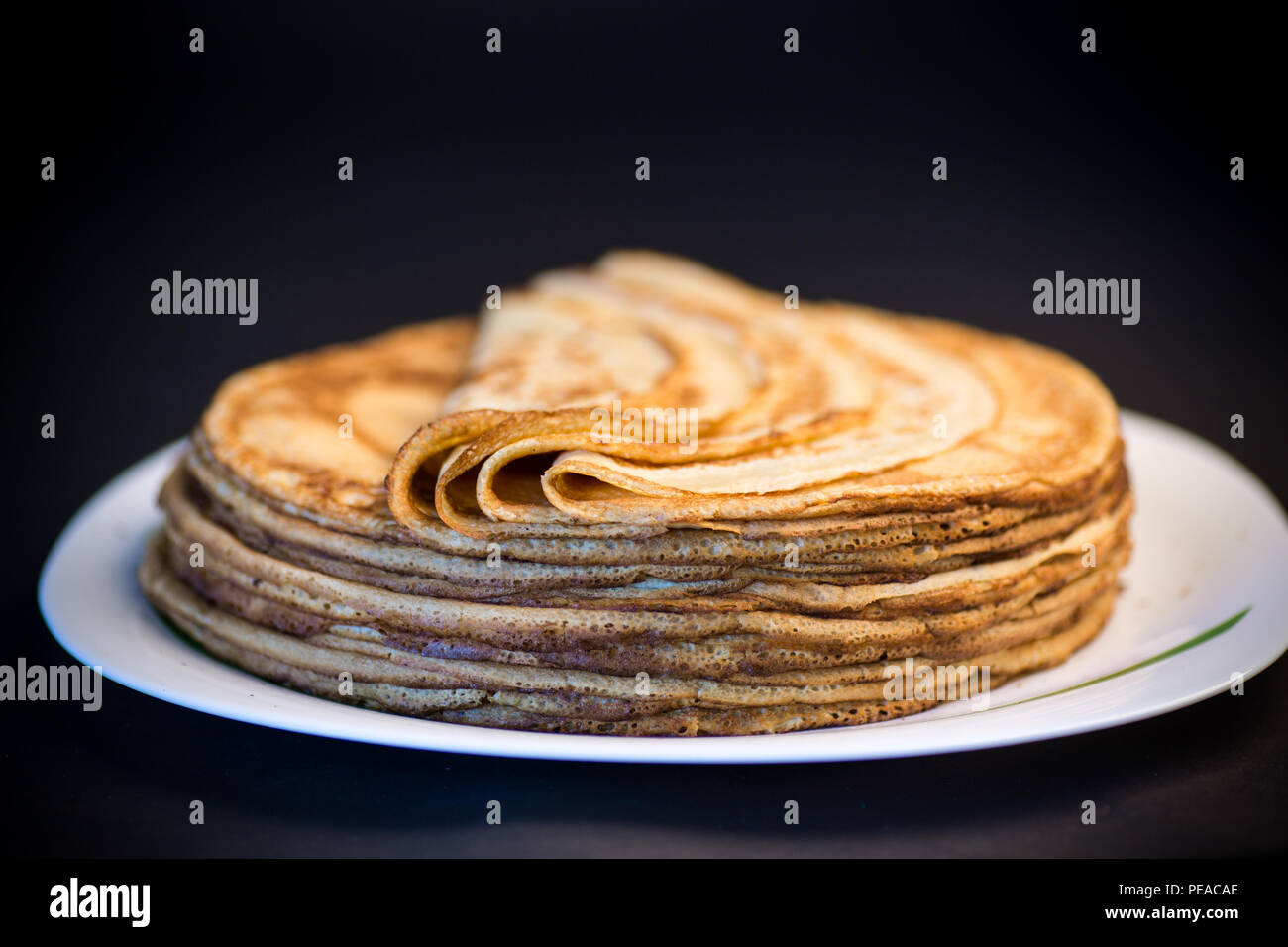 big high stack of thin pancakes in a plate on a black background - Stock Image