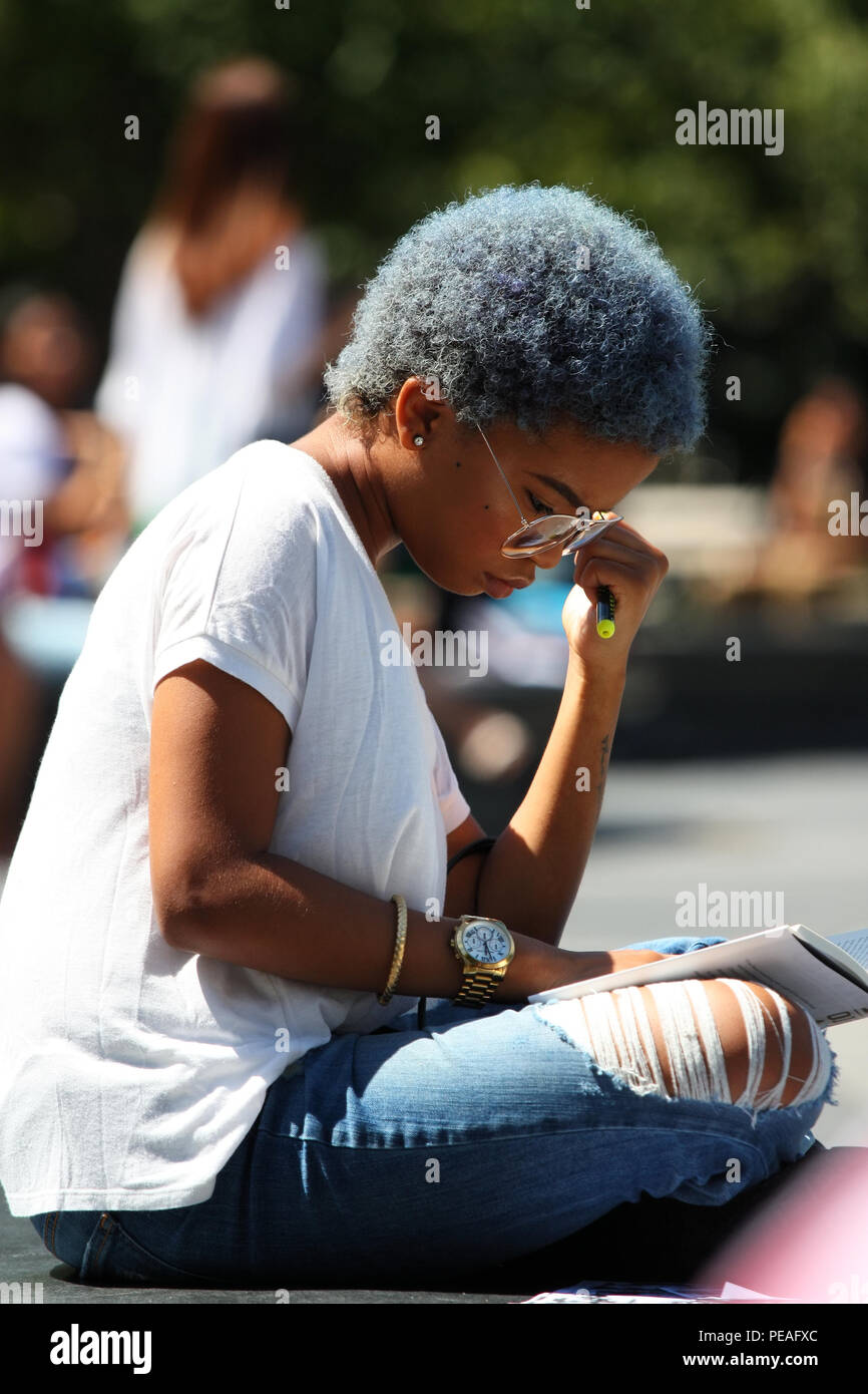 NEW YORK, NY - SEPTEMBER 02: Young black woman studying a book while sitting in Washington Square Park, Manhattan on September 2, 2016 in New York, US - Stock Image