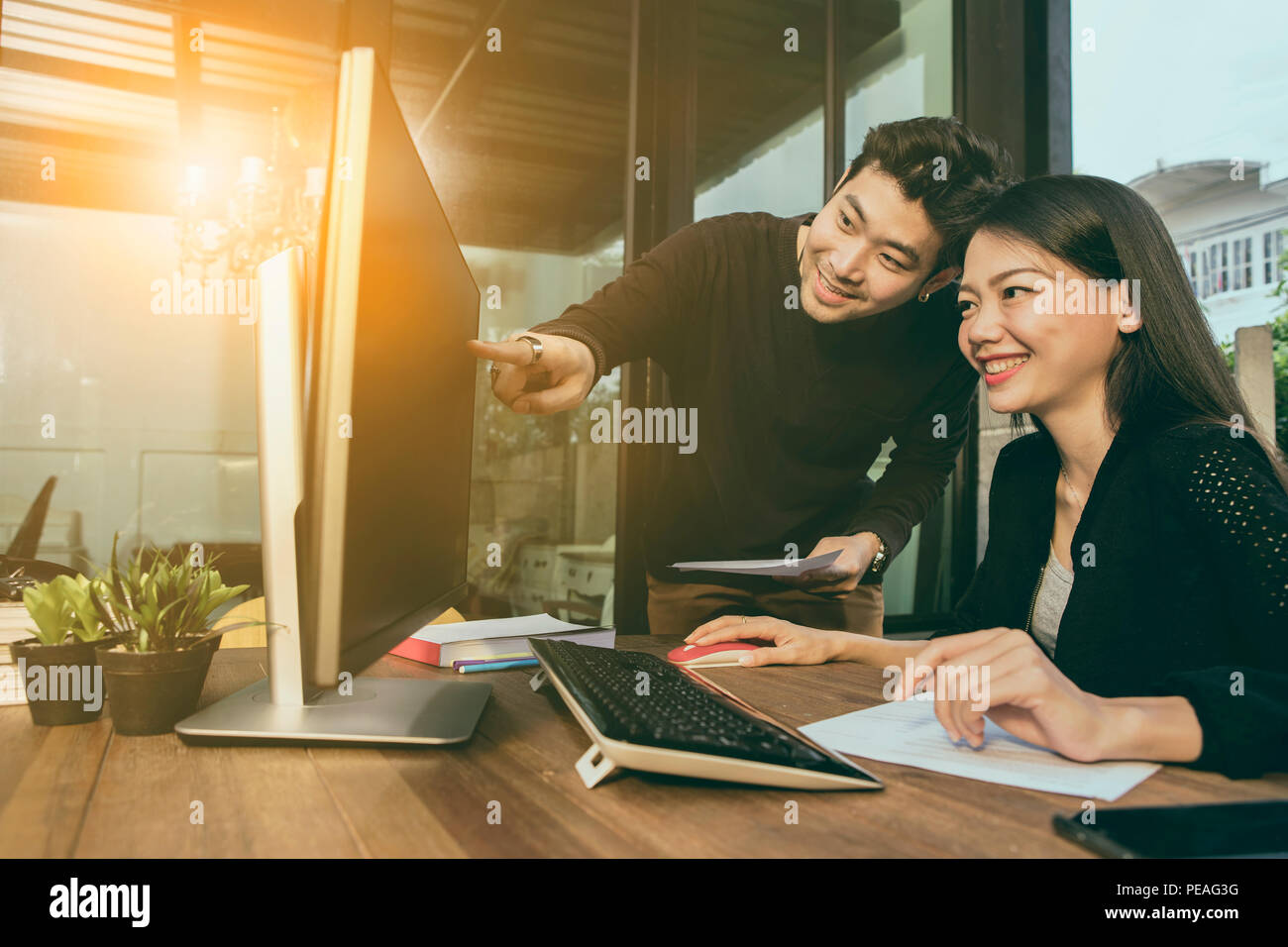 asian younger freelance man and woman working on computer at home office - Stock Image
