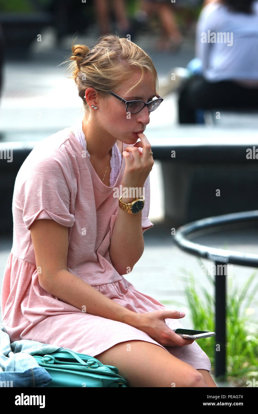 NEW YORK, NY - SEPTEMBER 05: Young white woman checks her phone while sitting in Washington Square Park, Manhattan on September 5, 2016 in New York, U - Stock Image
