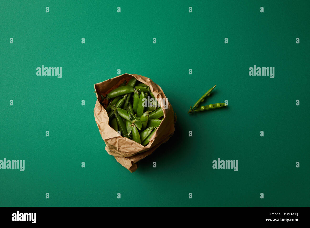 top view of paper bag with pea pods on green surface - Stock Image