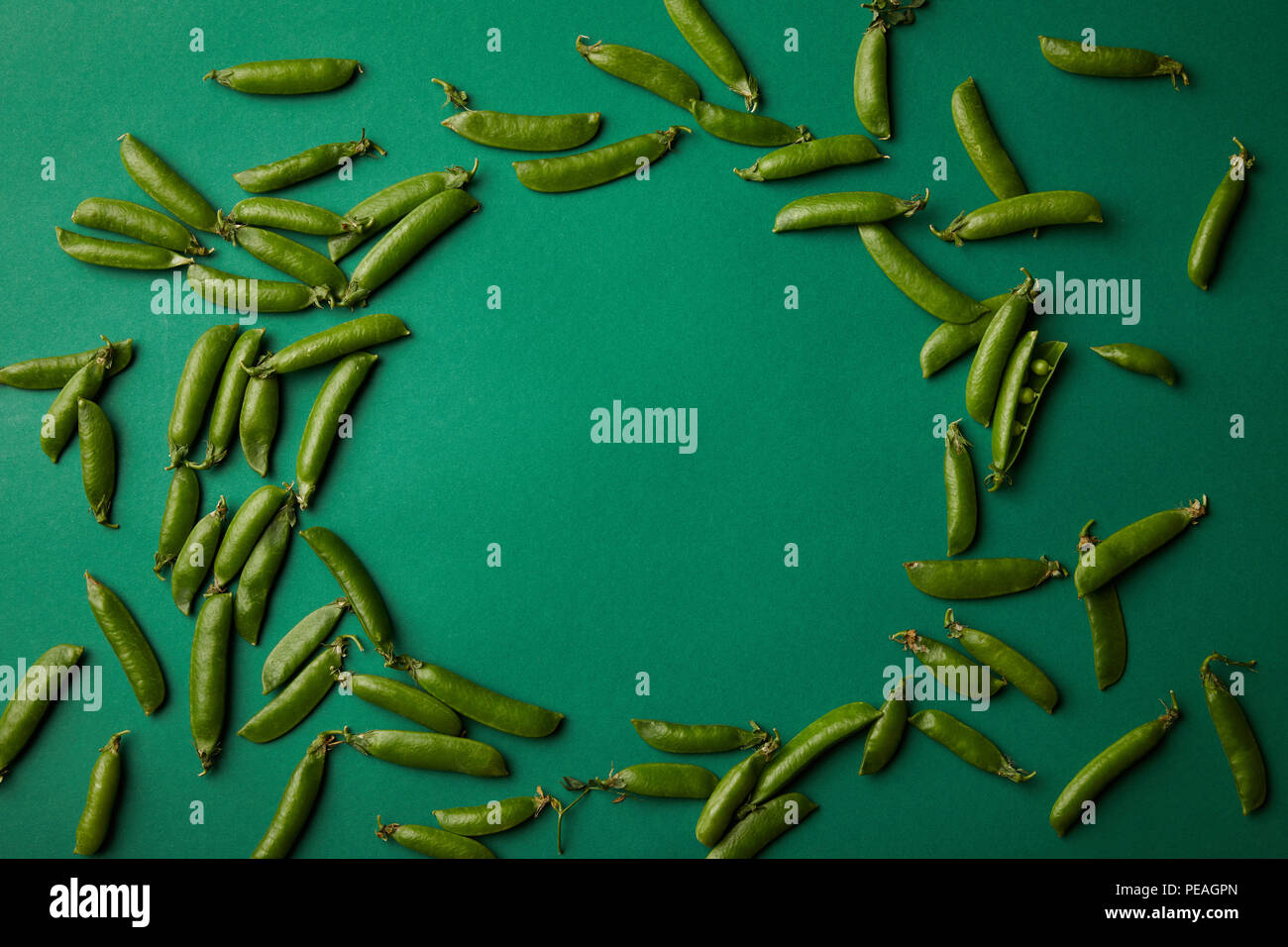 top view of round frame made of pea pods on green surface - Stock Image