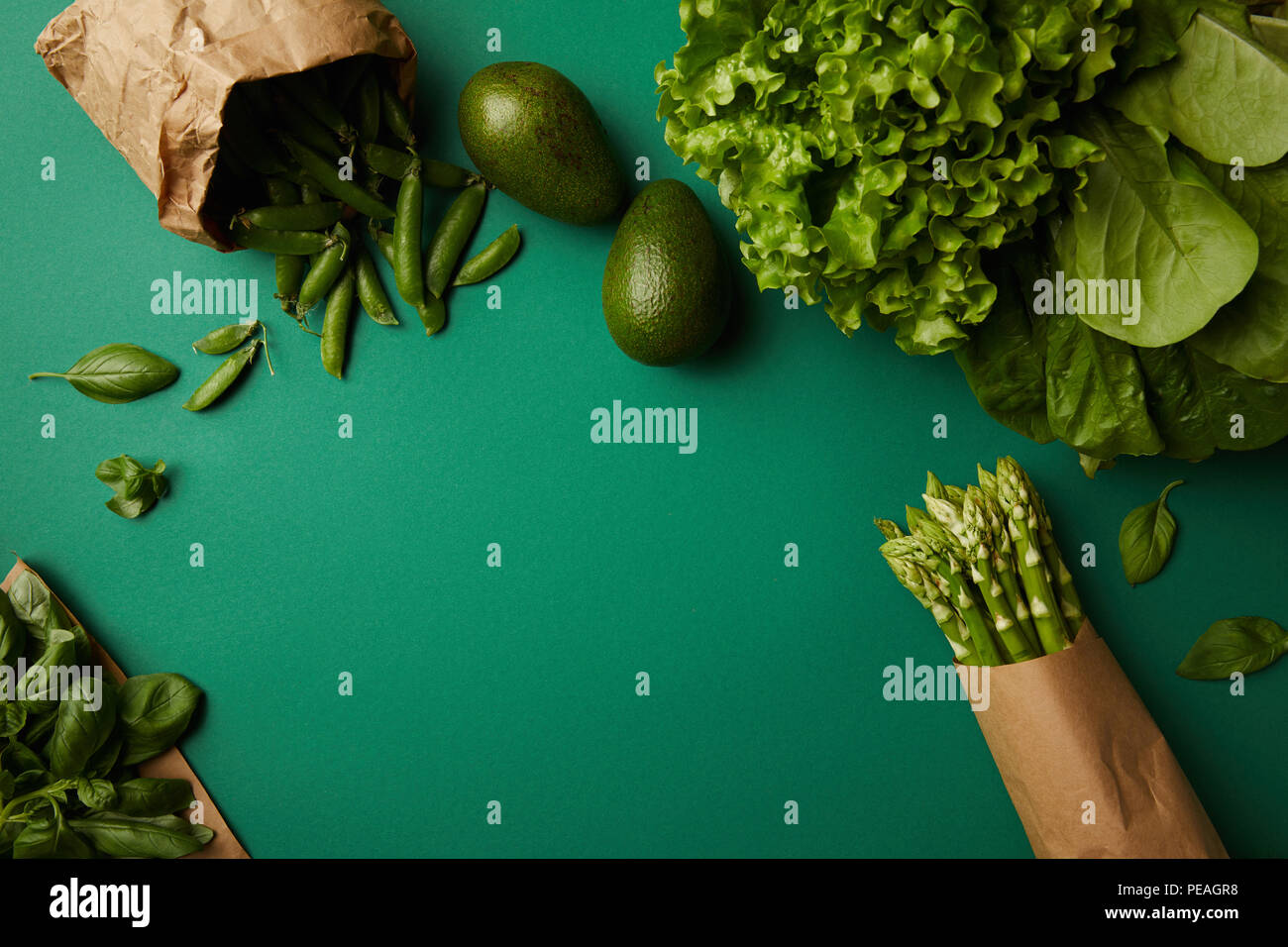 top view of different green ripe vegetables on green surface - Stock Image