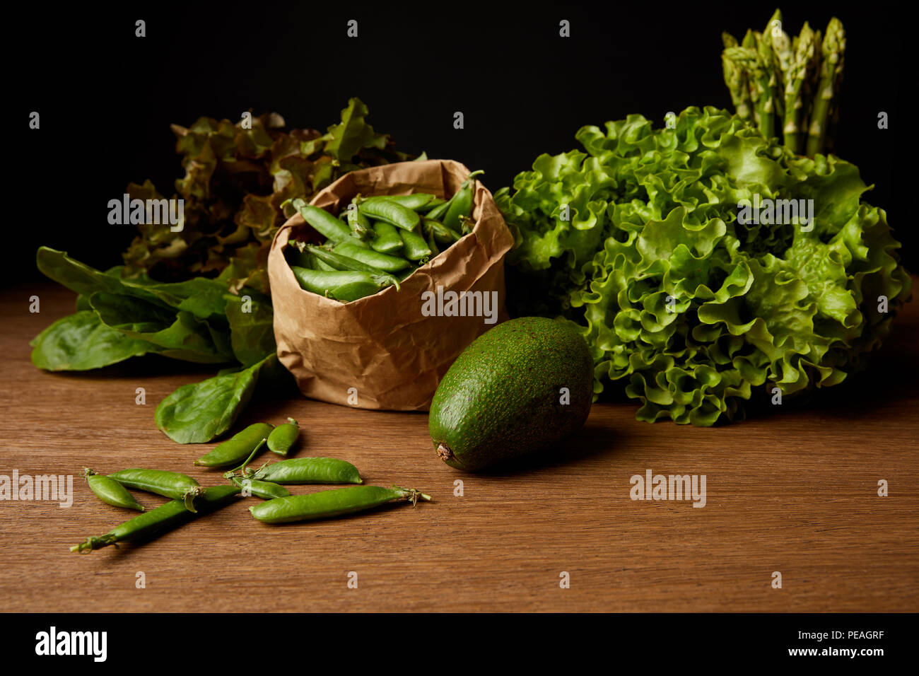 close-up shot of fresh green vegetables on wooden surface - Stock Image