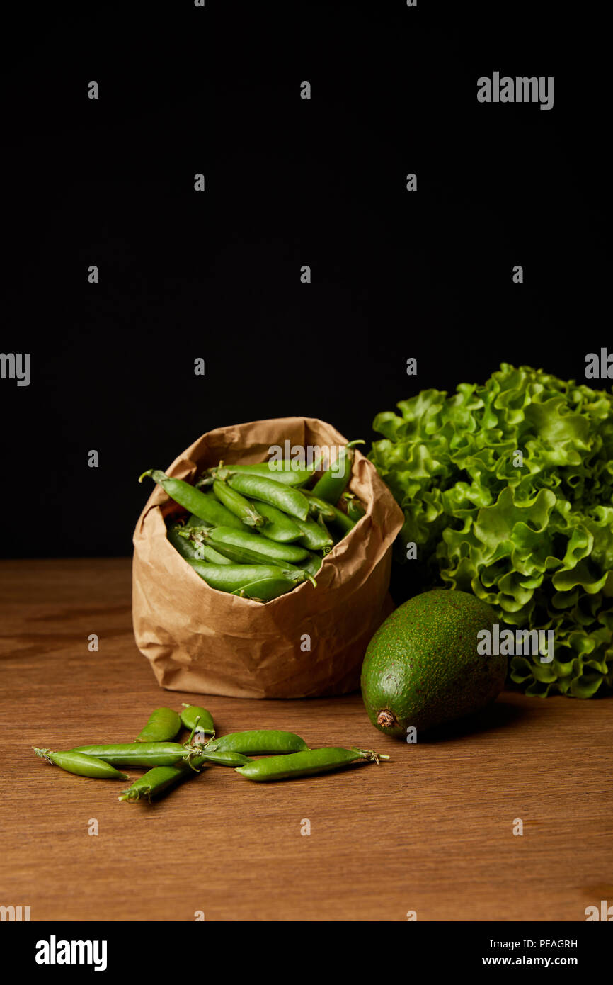 close-up shot of avocado, green peas and lettuce on wooden surface - Stock Image
