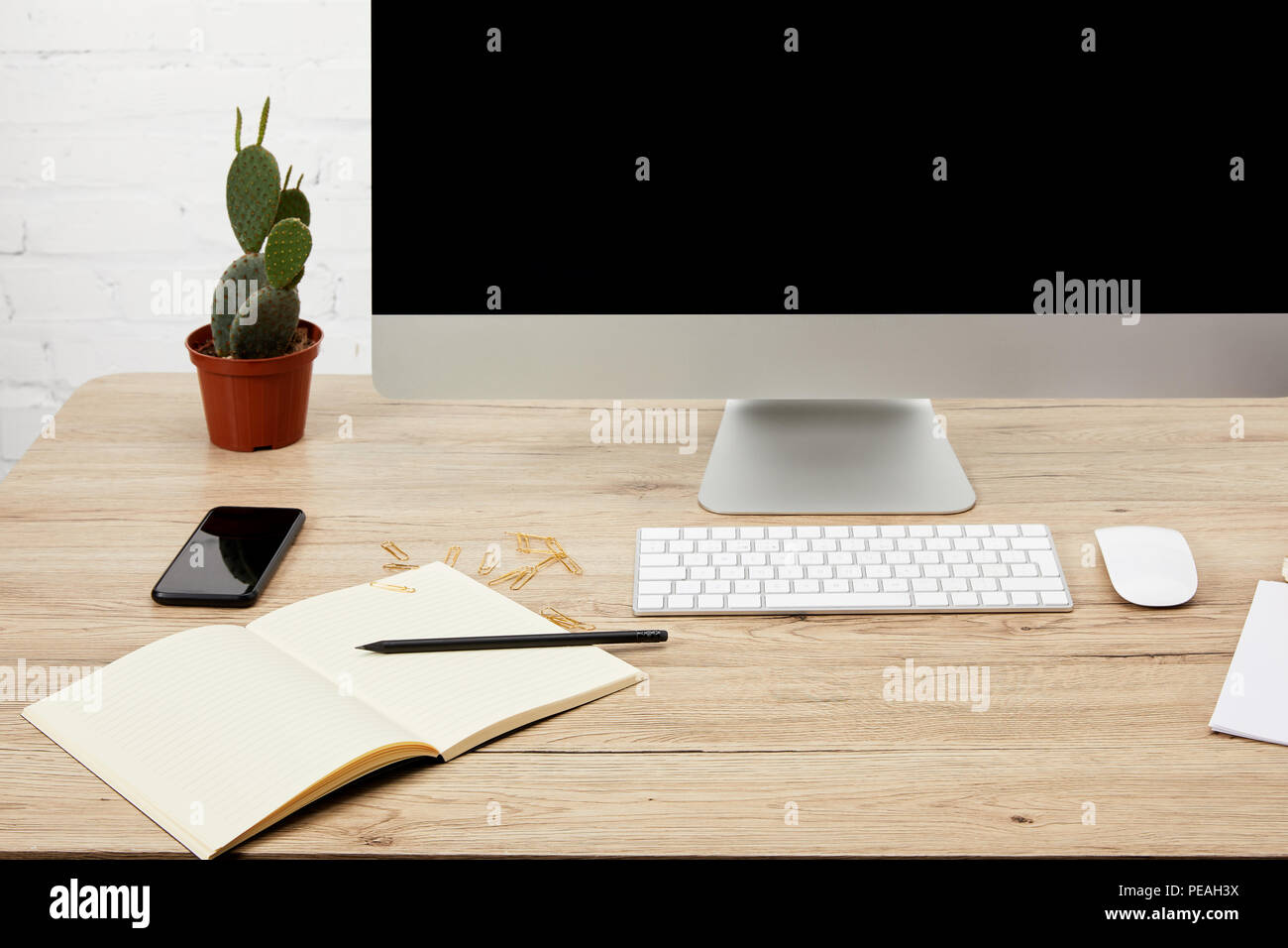 close up view of designer workspace with smartphone, notebook, computer screen and keyboard on wooden surface Stock Photo