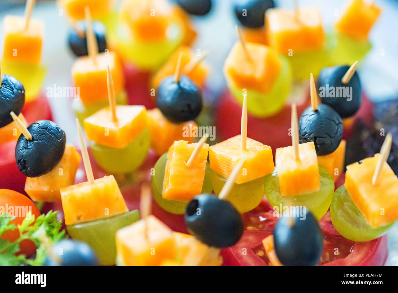Appetizer of cheese cubes, grapes and tomato - Stock Image