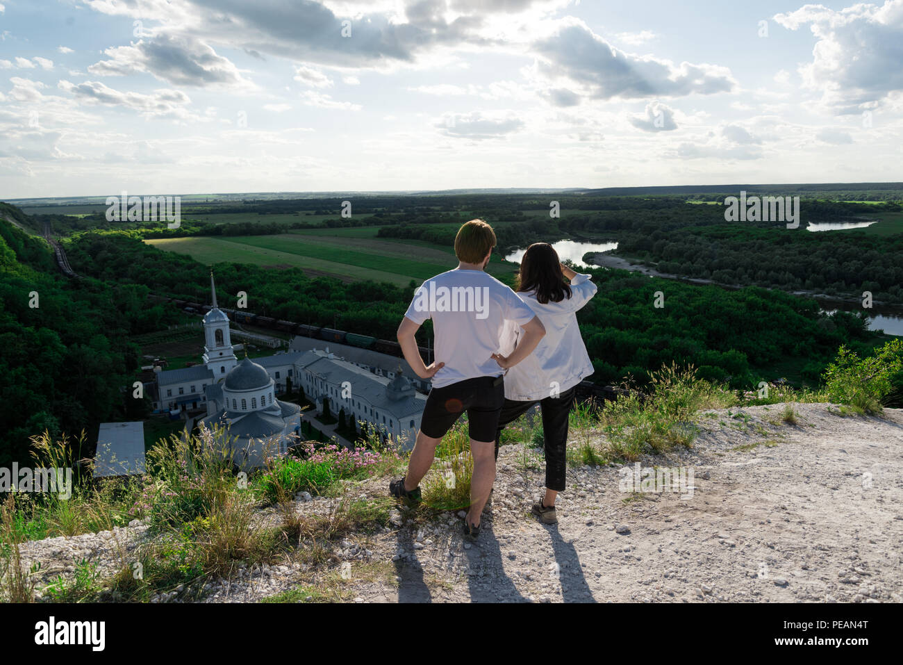 young couple travels standing on a hill and admiring the magnificent views of the valley, river and monastery - Stock Image