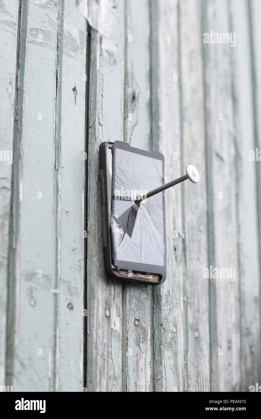 faulty mobile phone is nailed to an old fence - Stock Image