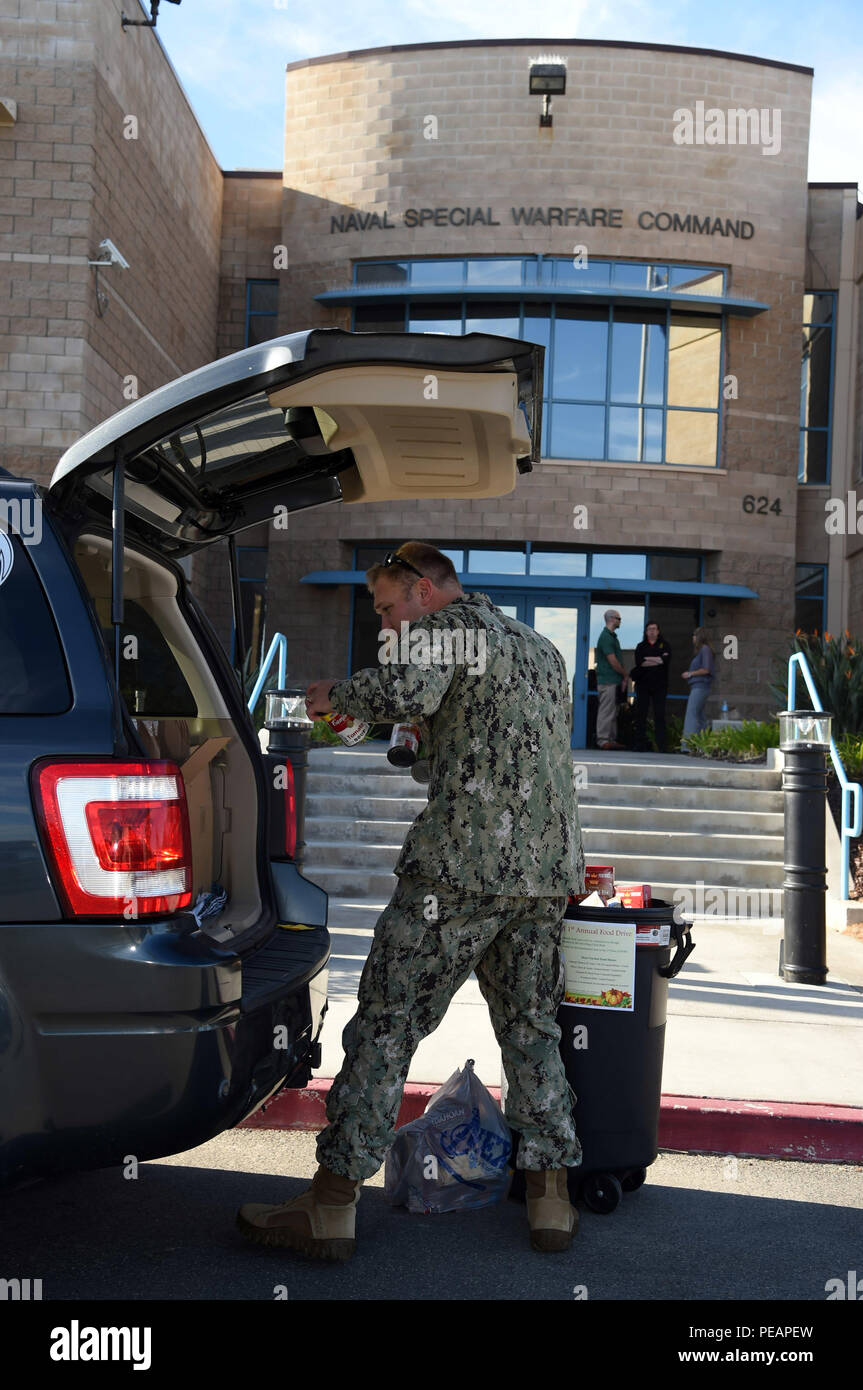 151120-N-AV746-015 CORONADO, Calif. (Nov. 20, 2015) Lt. Mike Gumpert, assigned to Naval Special Warfare Command, loads his vehicle with more than 700 food items donated by the command's Sailors and civilian staff. Gumpert organized the food drive in support of the San Diego Food Bank. (U.S. Navy photo by Mass Communication Specialist 2nd Class Timothy M. Black/Released) - Stock Image