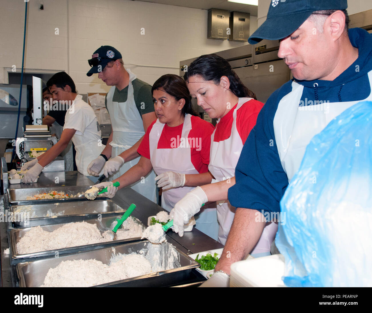 Members of the 149th Fighter Wing's Operations Group from Joint Base San Antonio served food onto microwave-safe food trays at a Meals on Wheels kitchen in San Antonio, Texas, Nov. 23, in preparation for the busy Thanksgiving week.  Older adults at least 60 years of age who are homebound, unable to cook for themselves and lack outside support are eligible to receive Meal on Wheels services. - Stock Image