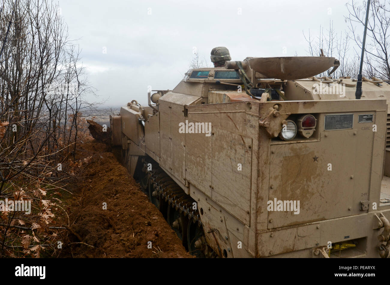 Spc. John McIntyre, a combat engineer attached to 5th Squadron, 7th Cavalry Regiment, 3rd Infantry Division, stationed at Fort Stewart, Ga., makes a hull-down battle position with an M9 Armored Combat Earthmover during Exercise Peace Sentinel at Novo Selo Training Center, Bulgaria, Nov. 23, 2015. (Photo by Staff Sgt. Steven M. Colvin/Released) - Stock Image